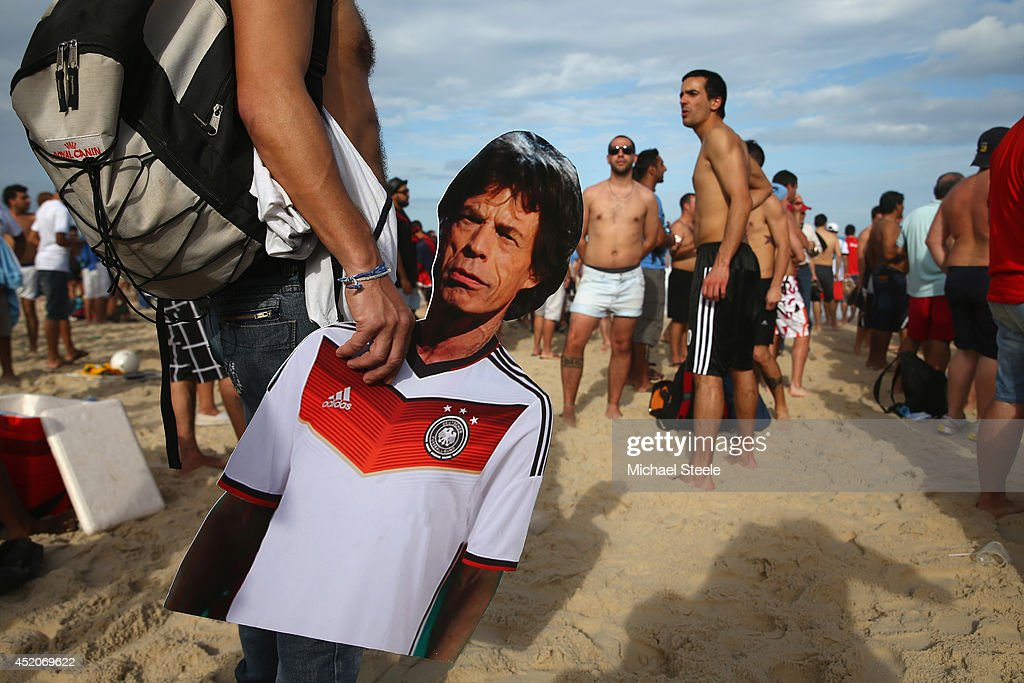 A supporter holds a cardboard cut out of Rolling Stones singer <a gi-track='captionPersonalityLinkClicked' href=/galleries/search?phrase=Mick+Jagger&family=editorial&specificpeople=201786 ng-click='$event.stopPropagation()'>Mick Jagger</a> in a German strip on Copacabana Beach ahead of the 2014 FIFA World Cup Brazil Final match on July 12, 2014 in Rio de Janeiro, Brazil.