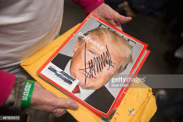A supporter holds a copy of TIME magazine he had signed by Republican presidential candidate Donald Trump during a rally at Des Moines Area Community...