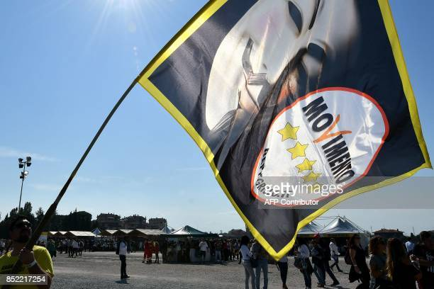 A supporter holds a flag showing the logo of Italy's populist Five Star Movement and a Guy Fawkes mask ahead of the party's congress in Rimini on...