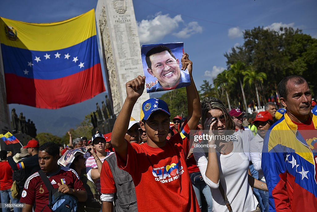 A supporter holds a photograph during the funeral for Venezuelan President Hugo Chavez in Caracas, Venezuela, on Friday, March 8, 2013. Allies of Venezuela's Hugo Chavez paid their final respects to the firebrand socialist leader at a state funeral that marked the emotional high point of a week of tributes preceding a snap election to choose his successor. Photographer: Meridith Kohut/Bloomberg via Getty Images