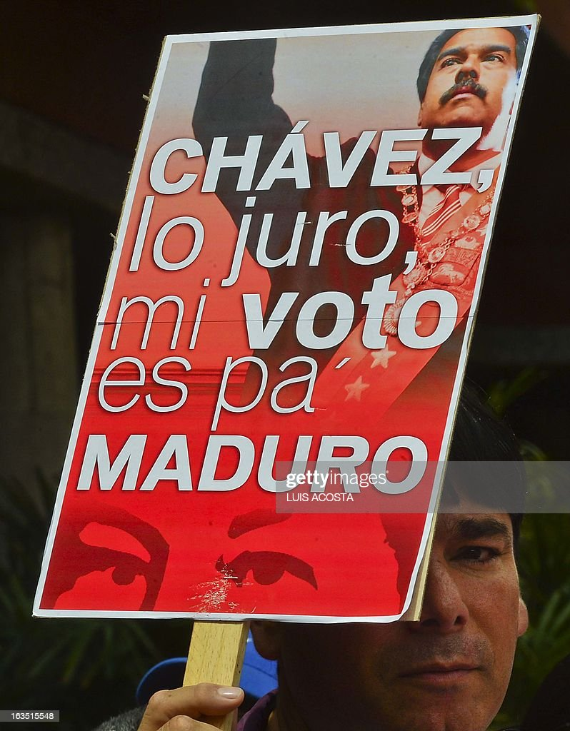 A supporter holds a placard supporting President in Charge Nicolas Maduro (not depicted) as he speaks during the official registration of his candidacy for the upcoming presidential election at the National Electoral Council (SNE) in Caracas, on March 11, 2013. Venezuela has entered a bitter election race to succeed Hugo Chavez, with his chosen successor branding his challenger a 'fascist' after the opposition candidate accused him of exploiting the late leader's death. AFP PHOTO/Luis Acosta