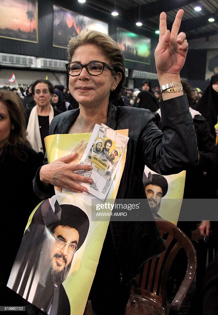 A supporter holds a poster of the former leader of Lebanon's Shiite Hezbollah movement Abbas alMussawi as they watch the current movement's leader...