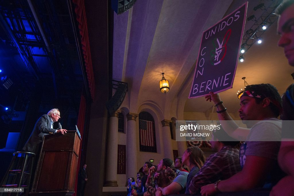 A supporter holds a Spanish language sign declaring unity with Democratic presidential candidate Bernie Sanders during a campaign rally at the Riverside Municipal Auditorium on May 24, 2016 in Riverside, California. US presidential candidates have turned their attention to campaigning in earnest for the June 7th California primary election. / AFP / DAVID