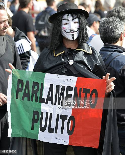M5S supporter holds an Italian national flag reading 'Clean Parliament' as he waits Antiestablishment 5Star Movement party leader Beppe Grillo on May...