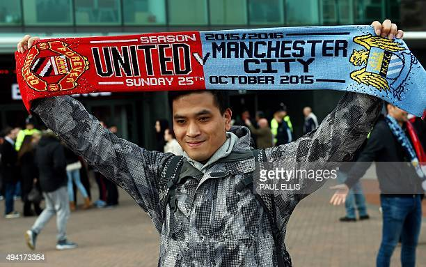A supporter holds up a half and half scarf ahead of the English Premier League football match between Manchester United and Manchester City at Old...