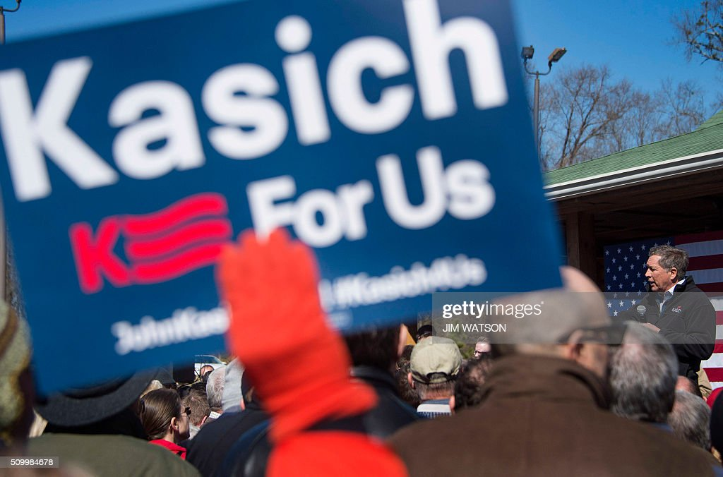 A supporter holds up a placard as Republican presidential candidate John Kasich speaks outside Mutt's BBQ in Mauldin, South Carolina, February 13, 2016. / AFP / JIM WATSON
