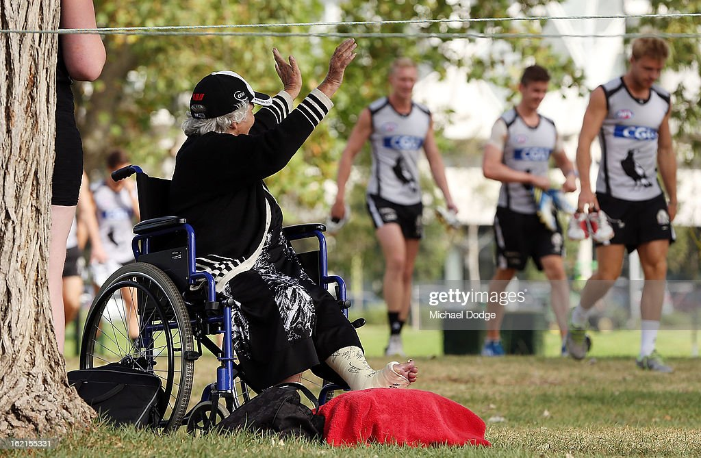 A supporter in a wheelchair waves to the players before a Collingwood Magpies AFL training session at Gosch's Paddock on February 20, 2013 in Melbourne, Australia.
