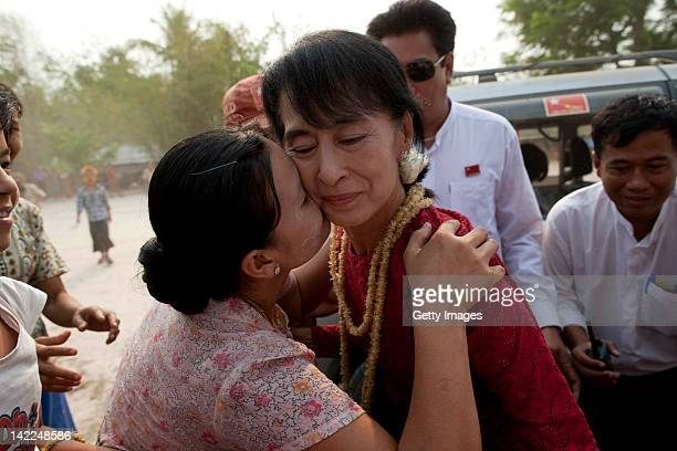 A supporter kisses Aung San Suu Kyi leader of the National League for Democracy as she visits polling stations in her constituency as Burmese vote in...