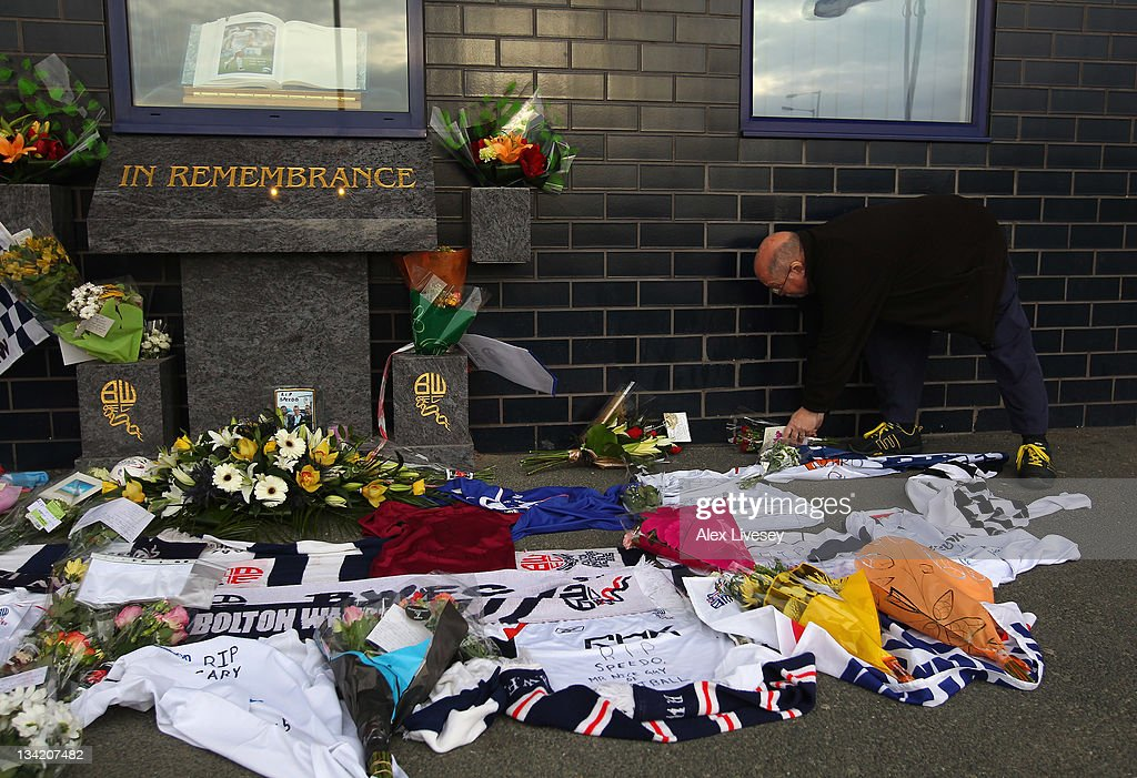 A supporter lays flowers amongst tributes to footballer and ex Bolton Wanderers player Gary Speed outside the Reebok Stadium the home ground of Bolton Wanderers FC on November 28, 2011 in Bolton, United Kingdom.