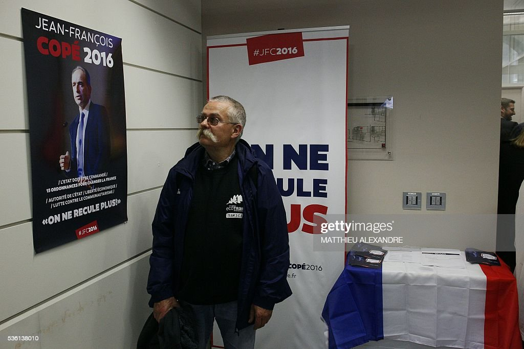A supporter looks at a campaign poster of French right-wing opposition Les Republicains (LR) party primary ahead of France's 2017 presidential elections, Jean-Francois Cope, during the election campaign headquarters' inauguration , on May 31, 2016, in Paris. / AFP / MATTHIEU