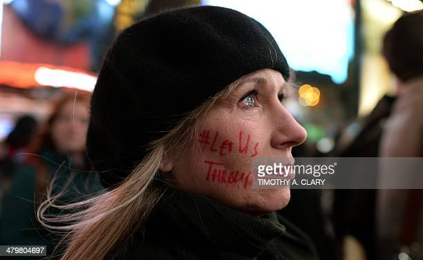 Supporter Lynn McCune watches during a flash mob on Times Square as an image of crowds of Palestinians lining up for UN Relief and Works Agency food...
