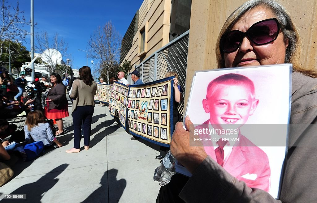 Supporter Maggie Storey holds a portrait of a boy called Eric, who went on to commit suicide at an older age, as Esther Miller (L rear) addresses the media outside the Cathedral of Our Lady of the Angels in Los Angeles, where abuse victims and their supporters gathered in Los Angeles, California, on February 1, 2013, one day after the release of personnel files of priests accused of sexual misconduct. The archbishop of Los Angeles Jose Gomez stripped his predecessor, retired Cardinal Roger Mahony, of all church duties on January 31. In all, 124 files were released on the Los Angeles archdiocese's website, listed by priests' names, including 82 containing information on allegations of childhood sexual abuse. AFP PHOTO / Frederic J. BROWN