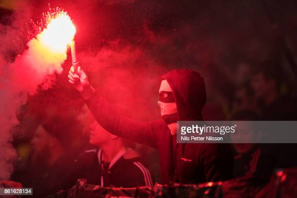 A supporter of AIK lights a flare during the Allsvenskan match between AIK and Jonkopings Sodra IF at Friends Arena on October 15 2017 in Solna Sweden