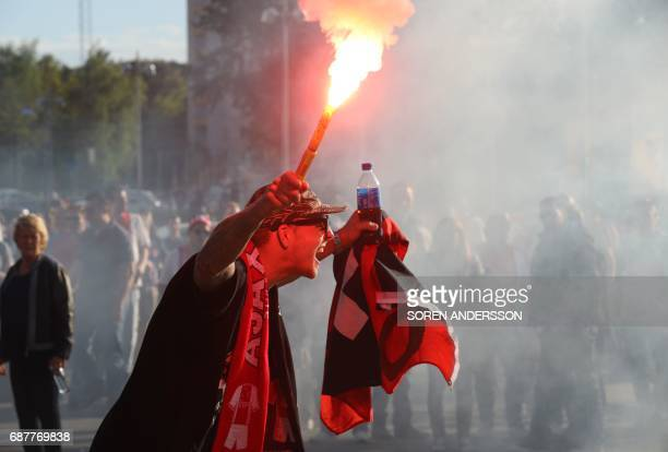 A supporter of Ajax Amsterdam holds a lit flare prior to the UEFA Europa League final football match Ajax Amsterdam v Manchester United on May 24...