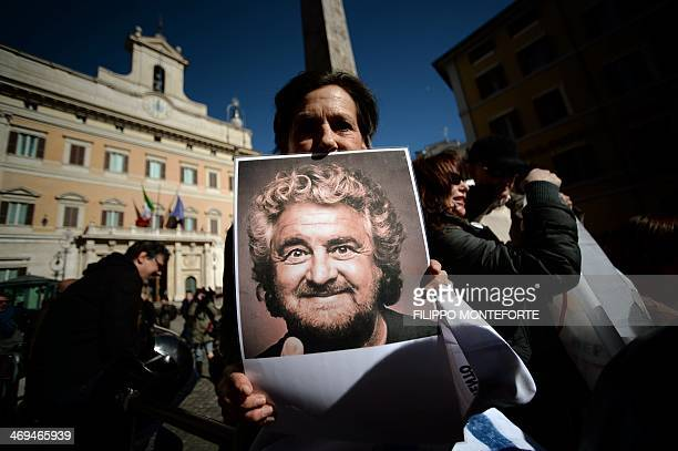 A supporter of antiestablishment party Five Star movement holds a portrait of its leader Beppe Grillo in front of the Montecitorio palace the Italian...