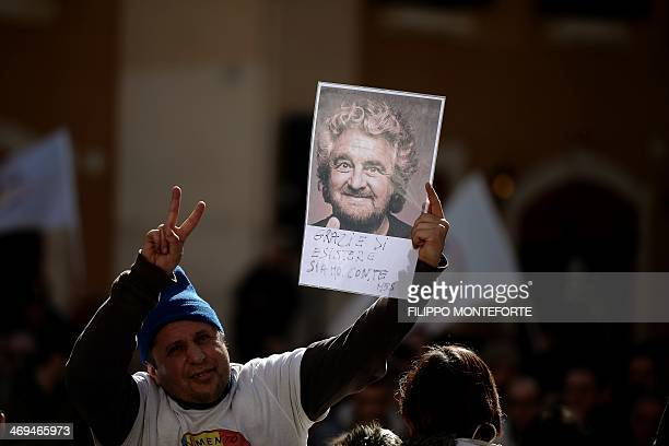 A supporter of antiestablishment party Five Star movement holds a portrait of its leader Beppe Grillo reading 'thanks for existing we are with you'...