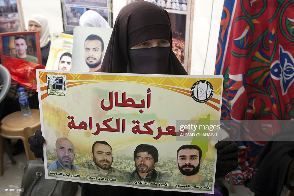 A Supporter of Arab-Israeli Islamist leader Sheikh Raed Salah, carries portraits of imprisoned Palestinians during a press conference by Sheikh Raed in east Jerusalem, on February 14, 2013. A United Nations official expressed concern about the well being of Palestinian detainees in Israeli prisons and in particular about the condition of hunger striker Samer Issawi. AFP PHOTO/AHMAD GHARABLI