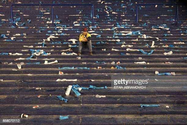 A supporter of Argentina sits on the stands at the end of the goalless 2018 World Cup football qualifier match against Peru in Buenos Aires on...