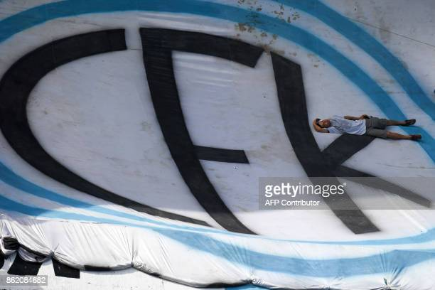 A supporter of Argentina's former President and Buenos Aires senatorial candidate for the Unidad Ciudadana Party Cristina Fernandez de Kirchner rests...