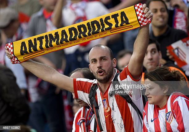 A supporter of Atletico de Madrid shows a scarf against Real Madrid before the UEFA Champions League quarter final football match Atletico de Madrid...