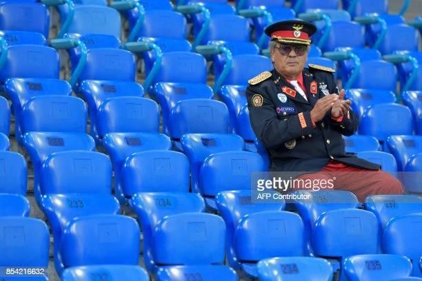 A supporter of Benfica wearing a selfmade uniform applauses during a training on the eve of the UEFA Champions league Group A football match between...