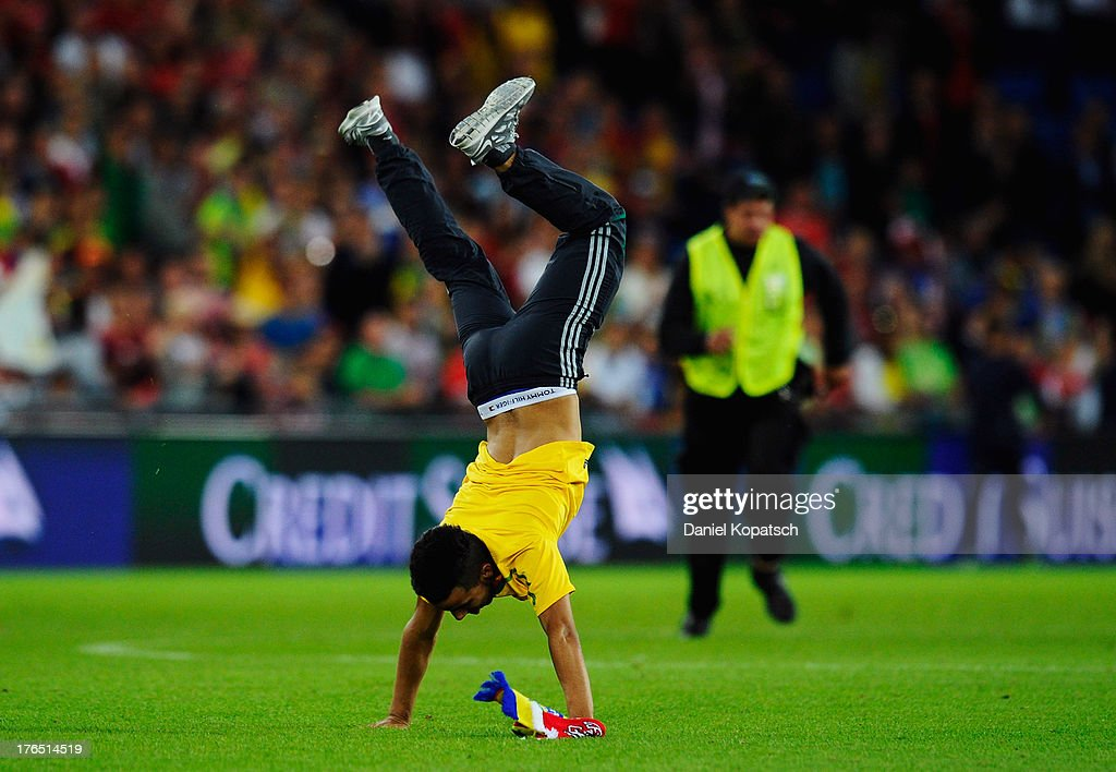 A supporter of Brazil runs onto the pitch and does a handstand after the international friendly match between Switzerland and Brazil at St. Jakob Stadium on August 14, 2013 in Basel, Switzerland.