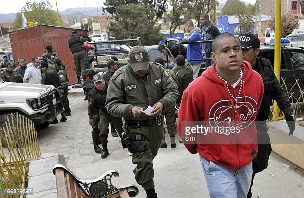 A supporter of Brazilian football team Corinthians is escorted as he enters San Pedro prison in Oruro Bolivia on April 17 2013 12 supporters of...