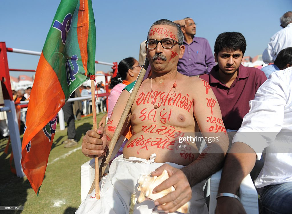 A supporter of Chief Minister of the western Indian state of Gujarat Narendra Modi poses with ' Aaj Ka CM Aur Kal Ka PM, Narendra Modi' which means 'Today's CM And Future's PM, Narendra Modi' written on his body as he participates in Modi's swearing in ceremony at The Sardar Patel Navrangpura Stadium in Ahmedabad on December 26, 2012. Modi who won a landslide victory in recent state assembly polls, was administered the oath of office and secrecy by Gujarat Governor Kamla Beniwal at a ceremony which was attended by many senior BJP leaders. AFP PHOTO/Sam PANTHAKY