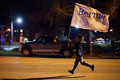 A supporter of Democratic presidential candidate US Sen Bernie Sanders runs with a banner near the site of the Democratic debate on February 4 2016...