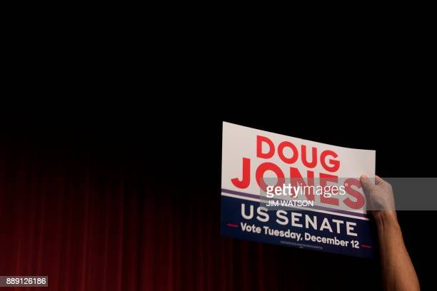 A supporter of Democratic Senatorial candidate Doug Jones holds up a placard during a rally in Birmingham Alabama on December 9 2017 The Alabama race...