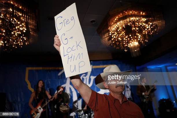 A supporter of Democratic US Congresstional candidate Rob Quist holds a sign that refers to Republican candidate Greg Gianforte during an election...