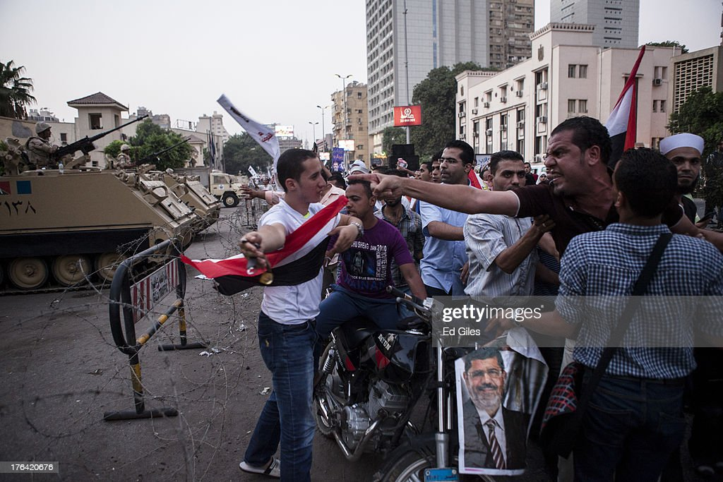 A supporter of deposed Egyptian President Mohammed Morsi is held back as he yells at nearby Egyptian Soldiers during a protest march in the Giza district on August 12, 2013 in Cairo, Egypt. Egyptian security forces threatened to begin a siege of pro-Morsi protest camps in Cairo overnight on August 11, however Egypt's Interior Ministry appeared to have put off plans to crack down on protesters early on August 12. On Monday Egypt's judiciary also extended deposed President Morsi's detention for a further 15 days pending investigation into charges of his collaboration with the Palestinian Hamas movement. Morsi supporters have continued to protest at sites across Cairo over one month after the Egyptian military deposed Egypt's first democratically elected President, Mohammed Morsi, on July 3. (Photo by Ed Giles/Getty Images).