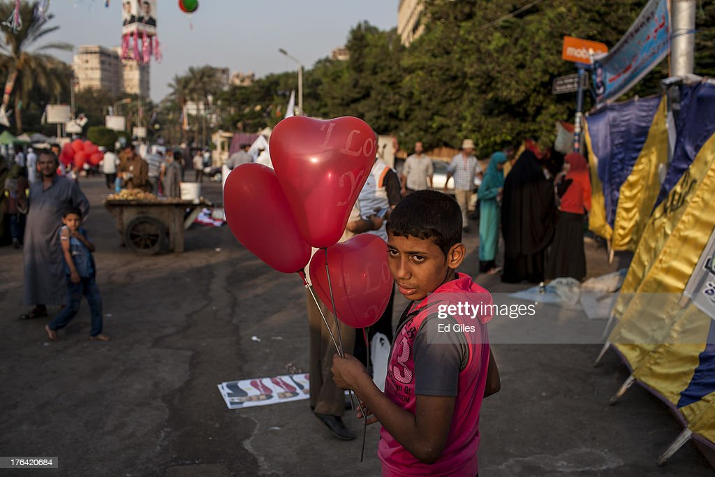 A supporter of deposed Egyptian President Mohammed Morsi sells balloons during a sit-in demonstration at Nahda Square in the Giza district on August 12, 2013 in Cairo, Egypt. Egyptian security forces threatened to begin a siege of pro-Morsi protest camps in Cairo overnight on August 11, however Egypt's Interior Ministry appeared to have put off plans to crack down on protesters early on August 12. On Monday Egypt's judiciary also extended deposed President Morsi's detention for a further 15 days pending investigation into charges of his collaboration with the Palestinian Hamas movement. Morsi supporters have continued to protest at sites across Cairo over one month after the Egyptian military deposed Egypt's first democratically elected President, Mohammed Morsi, on July 3. (Photo by Ed Giles/Getty Images).