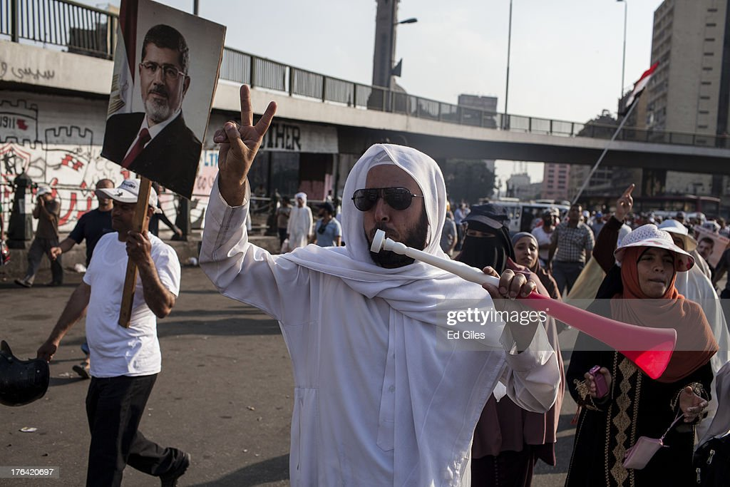 A supporter of deposed Egyptian President Mohammed Morsi uses a vuvzela horn during a protest march in central Cairo on August 12, 2013 in Cairo, Egypt. Egyptian security forces threatened to begin a siege of pro-Morsi protest camps in Cairo overnight on August 11, however Egypt's Interior Ministry appeared to have put off plans to crack down on protesters early on August 12. On Monday Egypt's judiciary also extended deposed President Morsi's detention for a further 15 days pending investigation into charges of his collaboration with the Palestinian Hamas movement. Morsi supporters have continued to protest at sites across Cairo over one month after the Egyptian military deposed Egypt's first democratically elected President, Mohammed Morsi, on July 3. (Photo by Ed Giles/Getty Images).