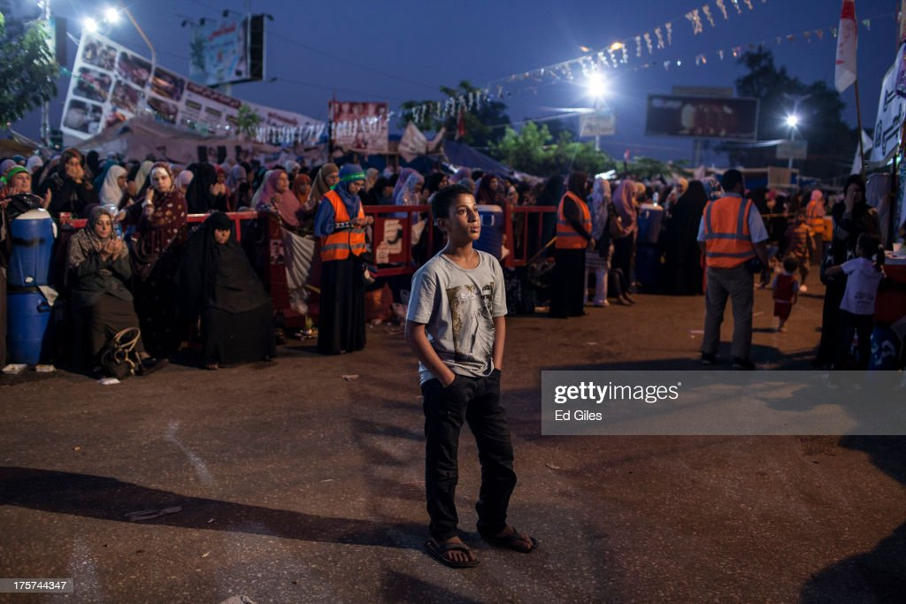 A supporter of deposed Egyptian President Mohammed Morsi watches a speaker on the stage prior to the 'Iftar' fastbreaking meal at a sitin protest at...