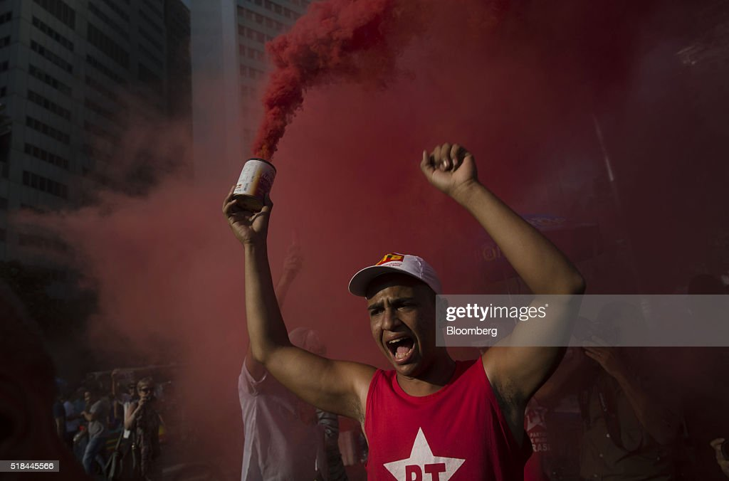 A supporter of Dilma Rousseff Brazil's president not pictured cheers while holding a can letting out red smoke during a demonstration in Rio de...