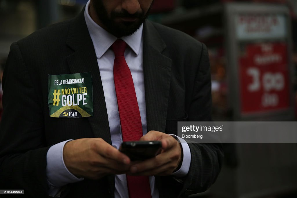 A supporter of Dilma Rousseff Brazil's president not pictured wears a sticker reading 'For Democracy There Will Be No Coup' during a demonstration in...