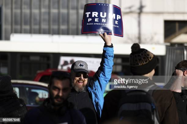 A supporter of Donald Trump hold a banner as demonstrators protest US military involvement in the Syrian war in Chicago United States on April 7 2017...