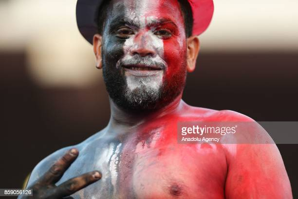 A supporter of Egypt with his face painted in the colours of Egyptian flag gestures as he poses for a photo during the 2018 World Cup Africa...