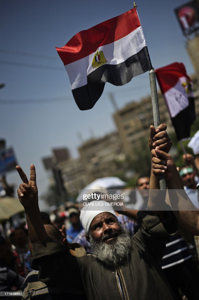 A supporter of Egyptian President Mohamed Morsi and the Muslim Brotherhood makes the victory sign while waving an Egyptian flag during a sitin to...
