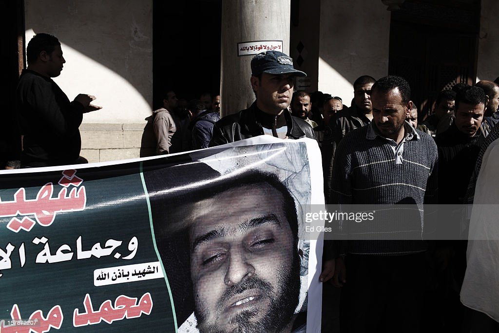 A supporter of Egyptian President Mohammed Morsi holds a banner depicting slain members of the Muslim Brotherhood during a funeral service for three Brotherhood members, killed in clashes with anti-Morsi demonstrators two nights previously, at Al Azhar Mosque on December 7, 2012, in Cairo, Egypt. A funeral service for three members of the Muslim Brotherhood was held during Friday prayers in Cairo before the bodies were carried to a nearby cemetery for burial. Supporters of President Morsi and anti-Morsi protesters continue to hold opposing demonstrations across Egypt, as tensions in the country remain high after a draft constitution was rushed through the country's parliament overnight on November 29. The country's new draft constitution, passed by a constitutional assembly dominated by Islamists, will go to a referendum on December 15. (Photo by Ed Giles/Getty Images).