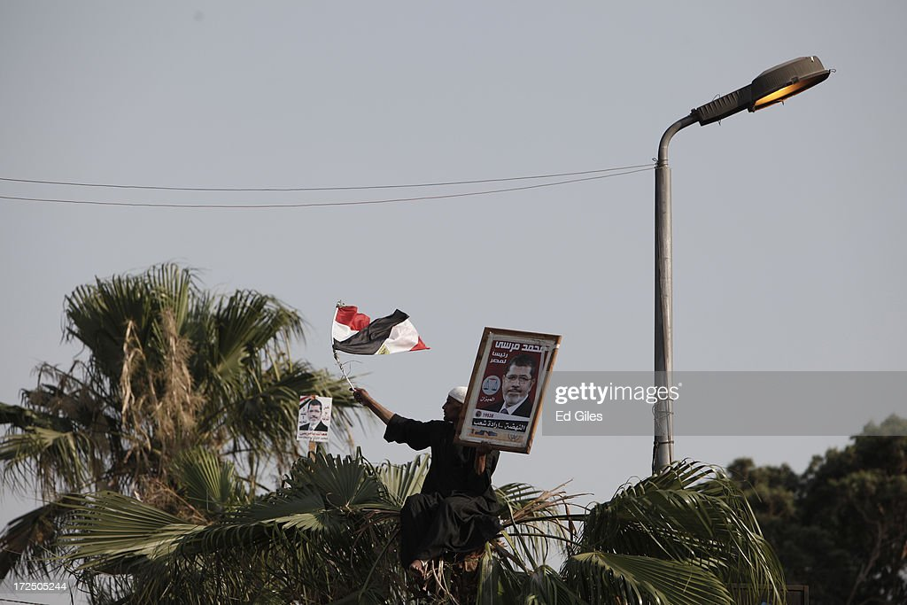 A supporter of Egyptian President Mohammed Morsi holds an Egyptian flag and a poster of Morsi during a demonstration at the Rabaa al Adawiya Mosque in the suburb of Nasr City on July 2, 2013 in Cairo, Egypt. In a statement on July 1, the Egyptian Army asked Egyptian President Mohammed Morsi to resolve mass demonstrations against his continued rule or face intervention by the military within 48 hours. Crowds of pro- and anti-government protesters gathered in locations across Egypt on June 30, the day of a series of nation-wide mass demonstrations entitled 'Tamarod', or 'Rebel'. The 'Tamarod' campaign, organised by a coalition of opposition political groups and planned to take place on the first anniversary of Egyptian President Mohammed Morsi's election to the country's Presidency, aims to bring down the government of President Morsi through country-wide demonstrations.