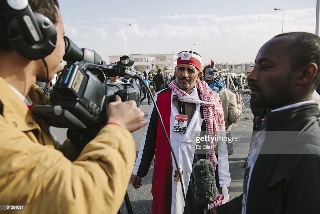 A supporter of Egypt's Defense Minister General Abdel Fattah al-Sisi speaks to a camera crew prior to the planned trial of deposed Egyptian President Mohammed Morsi at the Cairo Police Academy on January 8, 2014 in Cairo, Egypt. A number of supporters of Egypt's Muslim Brotherhood were arrested at the Cairo Police Academy on Wednesday while demonstrating against the trial, which was was adjourned by Egyptian officials to February 1, 2014 after bad weather in Alexandria reportedly prevented a helicopter transporting Morsi to the trial from taking off. (Photo by Ed Giles/Getty Images).