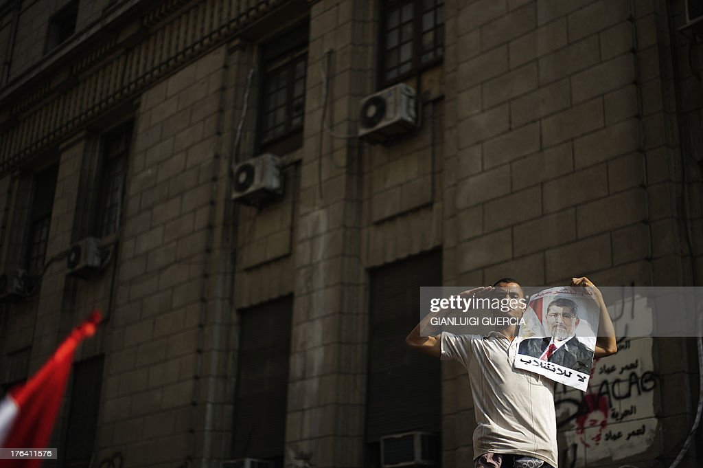 A supporter of Egypt's ousted president Mohammed Morsi holds a portrait of the former leader as he salutes during a demonstration outside the High Court in Cairo on August 12, 2013. Egypt's judiciary said it was extending Morsi's detention for a further 15 days pending an investigation into his collaboration with Hamas, which rules neighbouring Gaza.