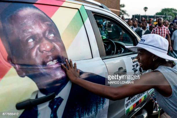 A supporter of Emmerson Dambudzo Mnangagwa touches an image of the politician glued on a SUV at the ZANUPF headquarter in Harare on November 22 2017...