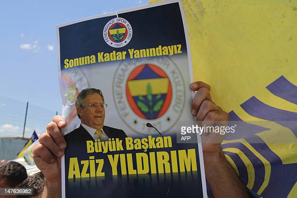 A supporter of Fenerbahce football club holds a placard reading 'Great President Aziz Yilidrim we are together until the end' as he celebrates the...