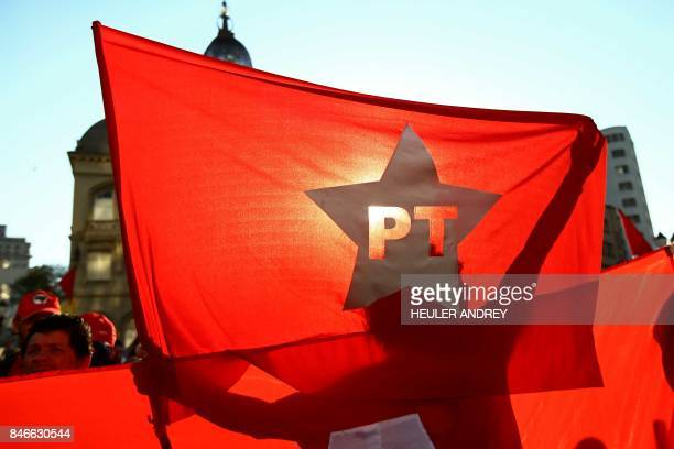 A supporter of former Brazilian president Luis Inacio Lula da Silva holds a Workers Party flag during a demonstration at Generoso Marques Square in...