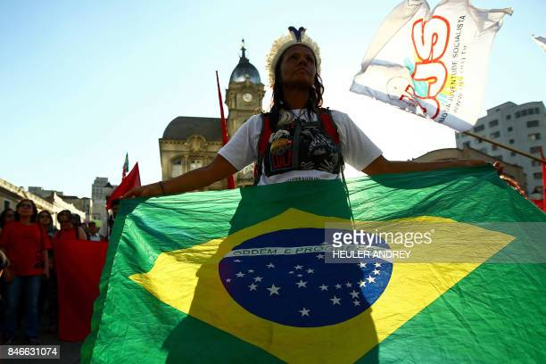 A supporter of former Brazilian president Luis Inacio Lula da Silva holds a Brazilian flag during a demonstration at Generoso Marques Square in...