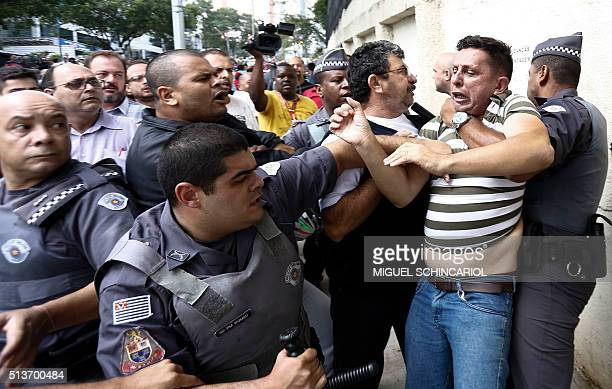 A supporter of former Brazilian president Luiz Inacio Lula da Silva who gathered with others outside his residence is restrained by PM militarized...