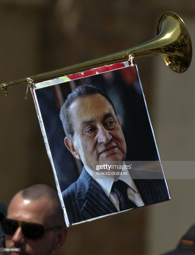 A supporter of former Egyptian president Hosni Mubarak, hangs his portrait on a trumpet outside the Egyptian police academy in Cairo, where Mubarak's trial is taking place on May 11, 2013. Mubarak appeared in court to face a new trial for complicity in the murder of hundreds protesters during the 2011 uprising.
